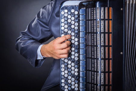 accordion: Musician playing the accordion against a black background Stock Photo