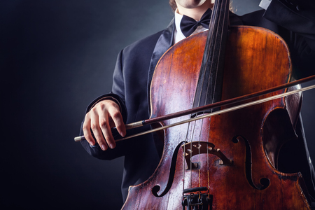 cellist: Cellist playing classical music on cello on black background