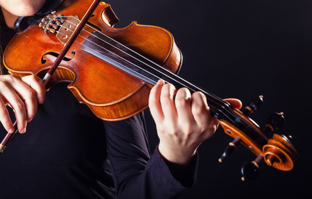 violin background: Playing the violin. Musical instrument with performer hands on dark background