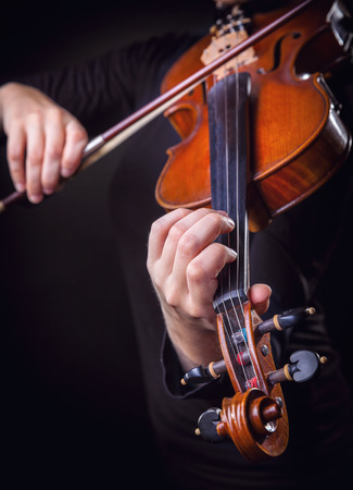 violin background: Playing the violin. Musical instrument with performer hands on dark background. Focus on the hand