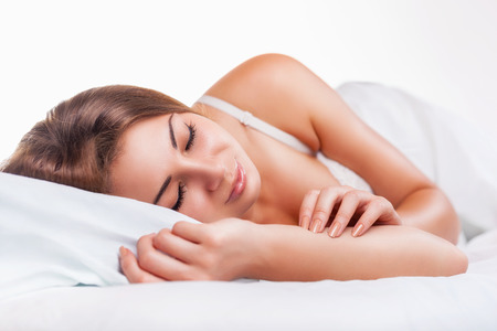 wellness sleepy: Attractive young woman sleeping in bed on a light background