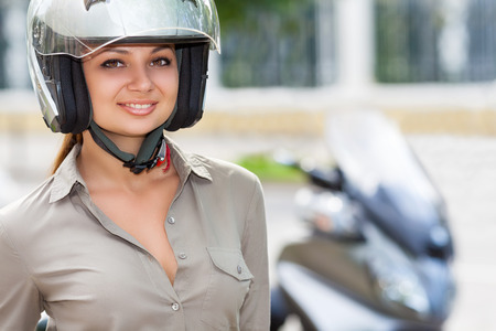 An attractive woman in a helmet on a background of city
