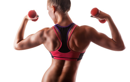 Muscular fitness girl with weights posing on a white background. Back view