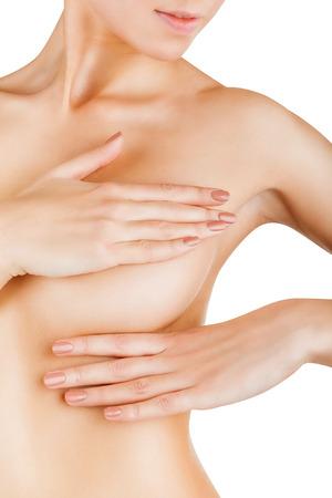 Junge Frau, die ihre Brüste für Anzeichen von Brustkrebs isoliert auf weißem Hintergrund