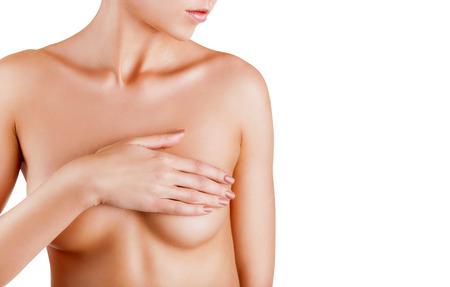 Schöne Frau, die ihre nackte Brust isoliert auf weißem Hintergrund