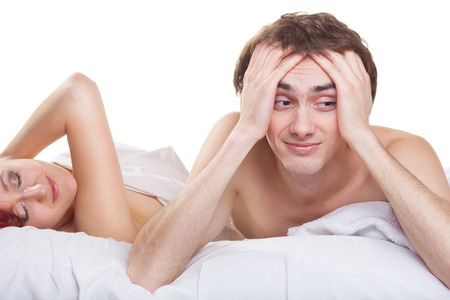 impotent: Upset man having problem on the bed with his wife on white background Stock Photo