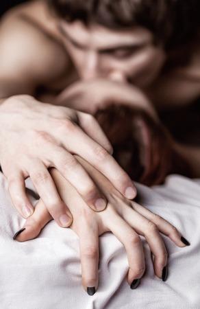 Junge schöne verliebten Paar Liebe machen im Bett. Fokus auf die Hände