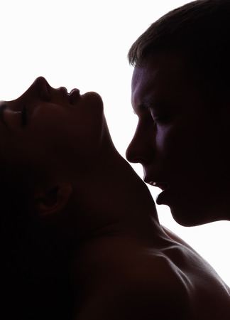 sex tenderness: Kissing young couple on a dark background