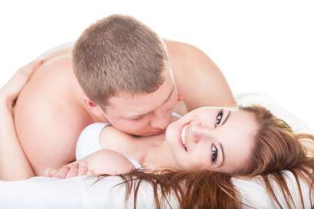 bed sex: Young beautiful amorous couple making love in bed on white background Stock Photo