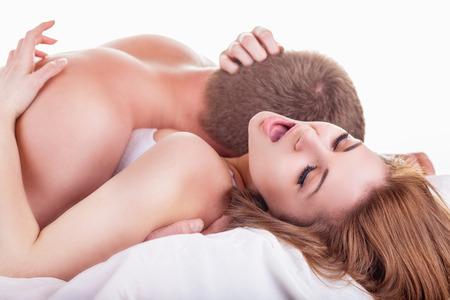 sex on bed: Young beautiful amorous couple making love in bed on white background Stock Photo