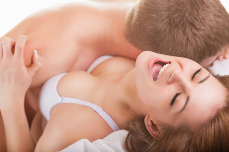 Young beautiful amorous couple making love in bed on white background Stock Photo
