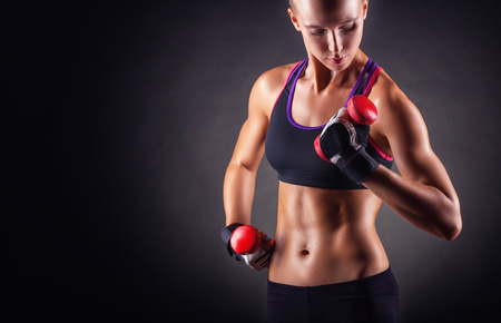 A young woman playing sports with weights on a dark background Stock Photo