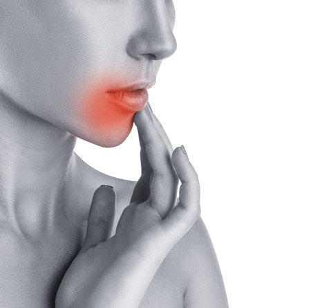 cold sore: Herpes concept. Close-up of young woman touching lips affected by herpes Stock Photo
