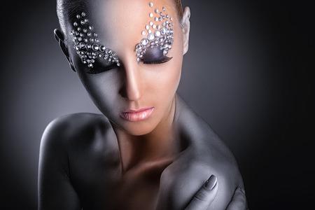 maquillaje de fantasia: Primer plano de una mujer joven con maquillaje de moda con diamantes de imitación en un fondo oscuro