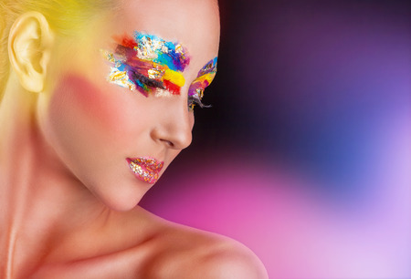 colorful paint: Young woman with colorful makeup on a colored background