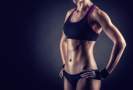 Young athletic woman on a black background