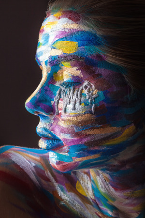 Young woman with colorful makeup and body art on a black background
