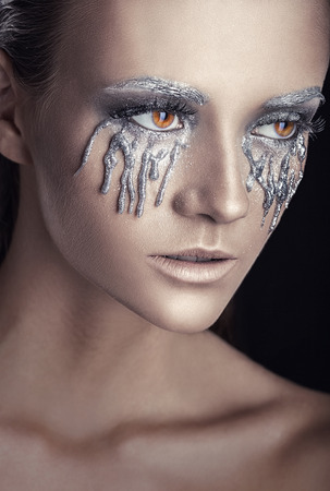 maquillaje de fantasia: Primer plano de una mujer hermosa con maquillaje de fantasía con lágrimas grises sobre fondo negro Foto de archivo