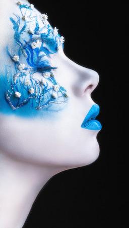 caritas pintadas: Mujer hermosa con maquillaje de la manera. Piel blanca con sombras azules y los labios en un negro