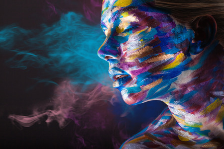 Young woman with colorful make-up and body art on a black with multi-colored smoke