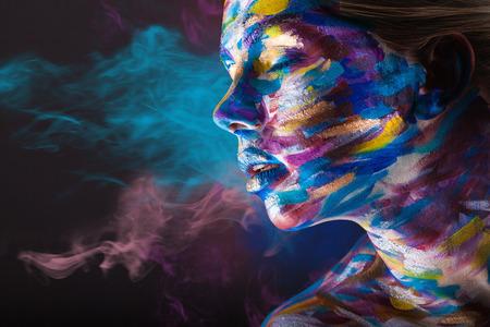 body paint: Mujer joven con maquillaje colorido y arte corporal en un negro de humo multicolor