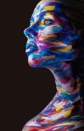 fantasy makeup: Mujer joven con maquillaje colorido y arte corporal en un negro Foto de archivo