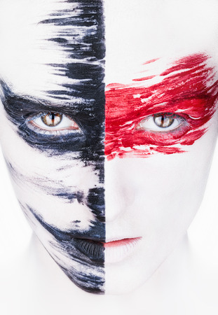 Close-up face of a beautiful woman with white makeup and red and black stripes paint