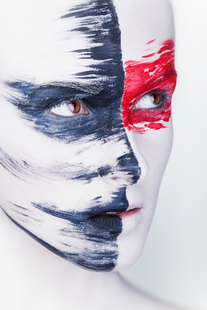 face paint: Close-up face of a beautiful woman with white makeup and red and black stripes paint