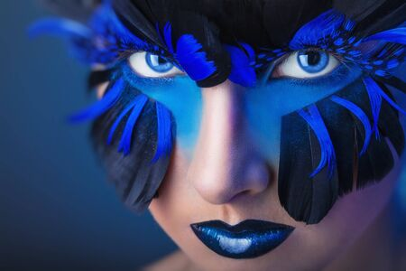 Beautiful woman with make-up with blue feathers Reklamní fotografie