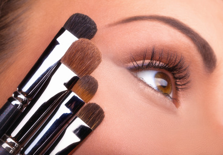 Close up of young womans face with various brushes for makeup