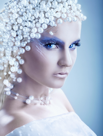 fantasy makeup: Portrait of beautiful woman with fantasy make-up with hair of white pearls on a blue  Stock Photo