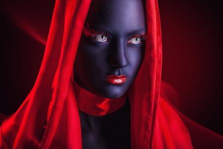 caritas pintadas: Mujer joven en una capa roja con maquillaje negro en una oscura