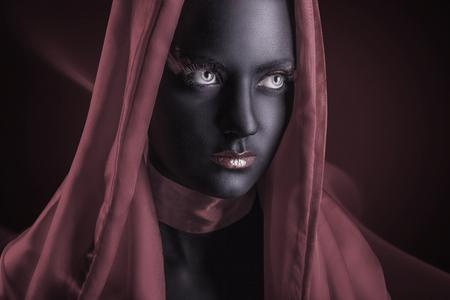 caritas pintadas: Mujer joven en una capa con maquillaje negro en una oscura