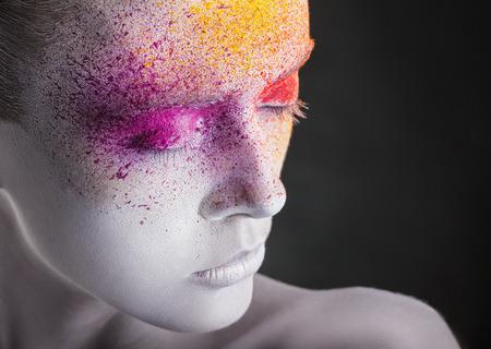 caritas pintadas: Primer plano de una mujer joven con maquillaje colorido sobre un fondo negro