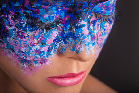 Close-up of a young woman with colorful makeup on a black  Foto de archivo