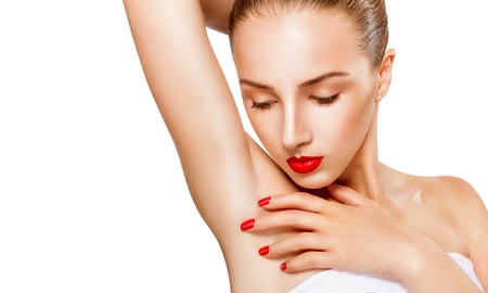 look at: Close-up of a beautiful young woman with makeup showing her smooth armpit isolated on white . Focus on the armpit