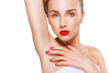Close-up of a beautiful young woman showing her smooth armpit isolated on white  Stock Photo