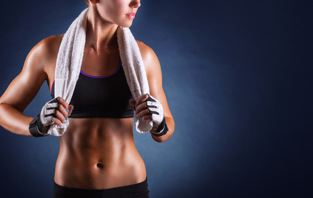 slim tummy: Young sports woman after workout with towel on his shoulders on a dark background Stock Photo