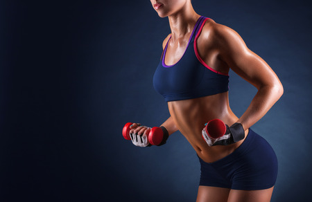 A young woman playing sports with weights on a dark