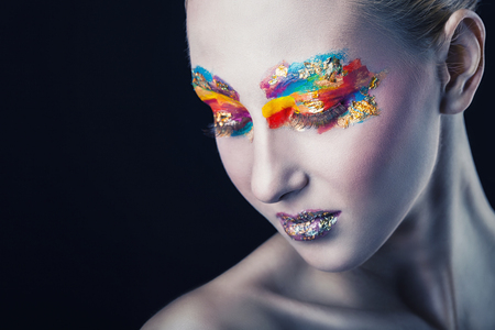 Beautiful woman with colorful makeup on black . Focus on the eye