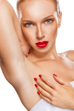 axila: Primer plano de una hermosa mujer pelirroja con lápiz labial rojo que muestra su axila suave. Aislado en el fondo blanco