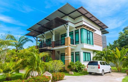 fachada: Casa moderna grande con el coche en el patio