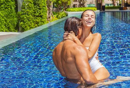 jovenes enamorados: Feliz pareja ba��ndose juntos en la piscina