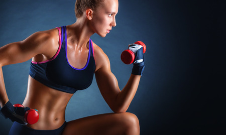 A young woman playing sports with weights on a dark background Imagens