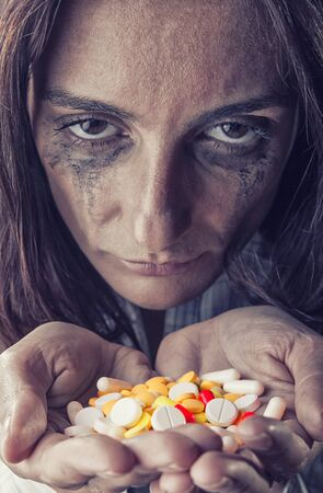 painkillers: Pills in womens hands on dark background. Focus on pills