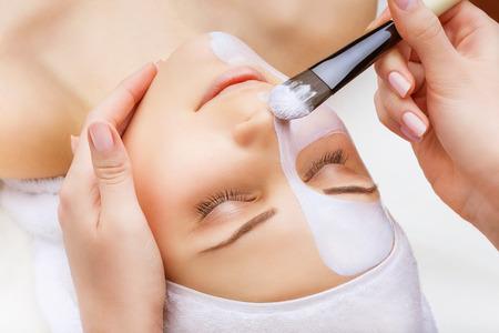 limpieza de cutis: La aplicación de la máscara facial en el rostro de la mujer sobre un fondo blanco