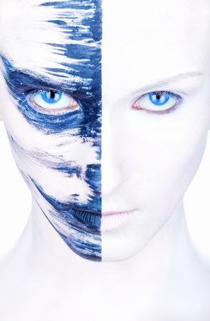 caritas pintadas: Primer plano de la cara de una mujer hermosa con maquillaje blanco y rayas de pintura azul Foto de archivo