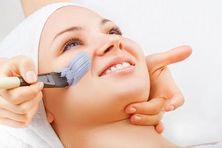 masaje facial: Mujer hermosa con la máscara facial en el salón de belleza