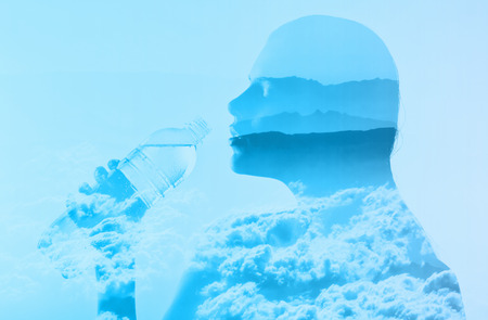 conceptual cute: Double Exposure of a beautiful woman with a bottle of water in combination with a photo of nature Stock Photo