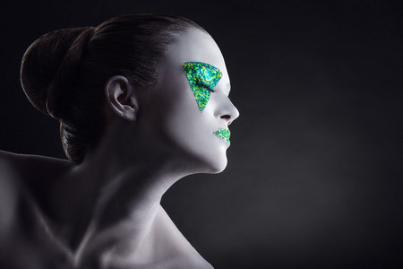 Young woman with colorful green makeup on black background Stock Photo